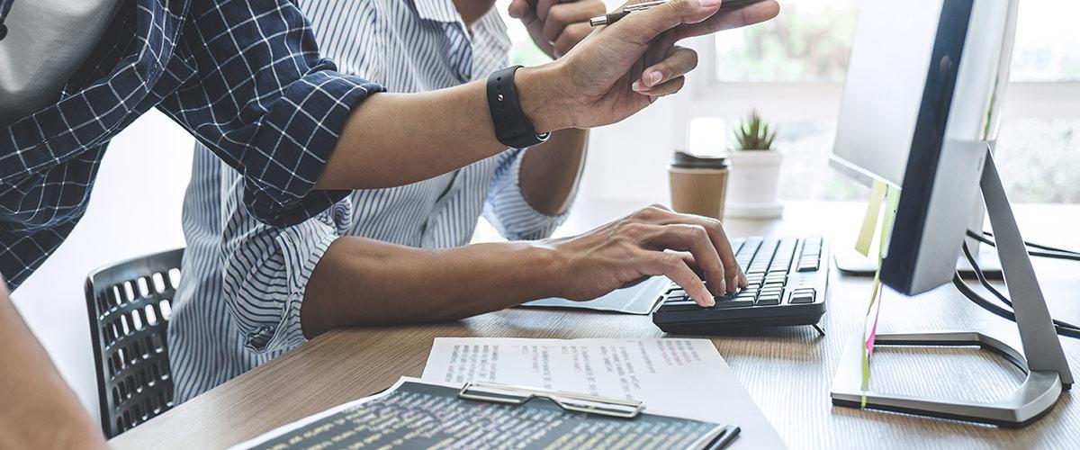 Zwei Personen, die auf einen PC Bildschirm zeigen