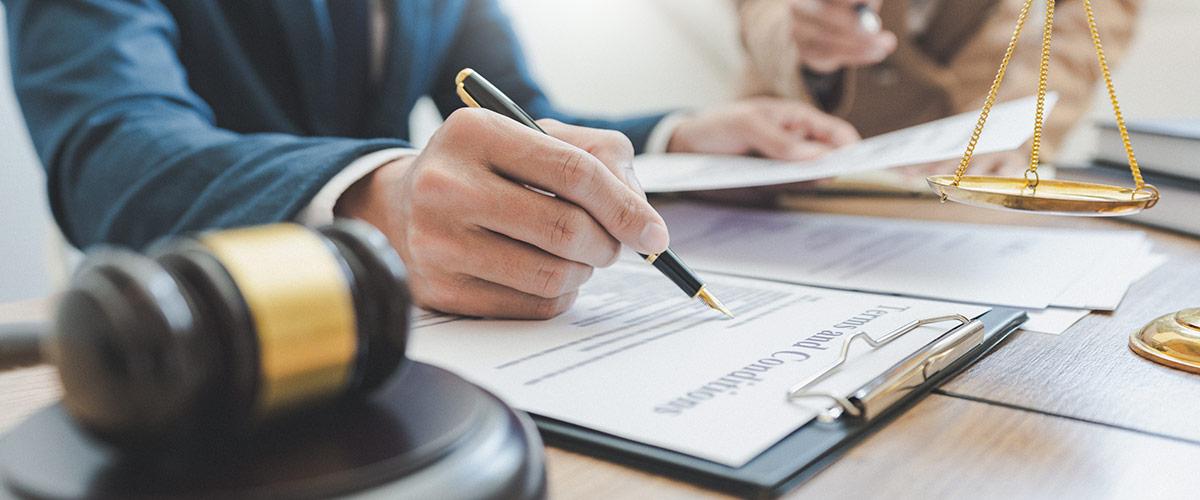 Person die einen Vertrag unterschreibt mit Richterhammer im Vordergrund